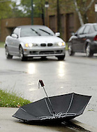 As the rain falls, an umbrella lies unused with no one around, across from the fire station on Wayne Avenue in the Belmont area of Dayton, Wednesday, June 4, 2008.