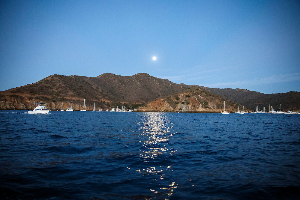 The moon sets during the Catalina Classic Paddle board race between Two Harbors and the Manhattan Beach Pier on Sunday, August 30, 2015 in Two Harbors, Calif.  Paddlers start from Two Harbors on Catalina Island, traveling 32 miles through the Pacific Ocean in an endurance feat to end at the Manhattan Beach Pier. © 2015 Patrick T. Fallon