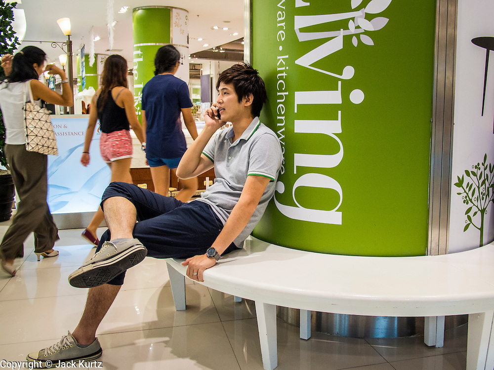 """24 AUGUST 2013 - BANGKOK, THAILAND: A man talks on his cell phone in a shopping mall in Bangkok. Thailand entered a """"technical"""" recession this month after the economy shrank by 0.3% in the second quarter of the year. The 0.3% contraction in gross domestic product between April and June followed a previous fall of 1.7% during the first quarter of 2013. The contraction is being blamed on a drop in demand for exports, a drop in domestic demand and a loss of consumer confidence. At the same time, the value of the Thai Baht against the US Dollar has dropped significantly, from a high of about 28Baht to $1 in April to 32THB to 1USD in August.     PHOTO BY JACK KURTZ"""