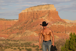 shirtless sexy young cowboy wearing chaps outdoors in New Mexico sexy cowboy with an open shirt walking in Abiquiu at sunset