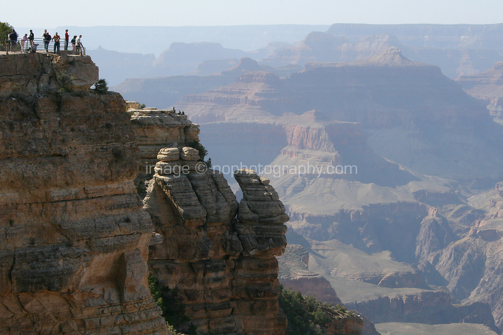 Tourists viewing of The Grand Canyon from the South Rim in Arizona USA. One of the Seven Natural Wonders of the World, the canyon was created by the Colorado River millions of years ago. The canyon is 277 river miles long, up to 18 miles wide and a mile deep.