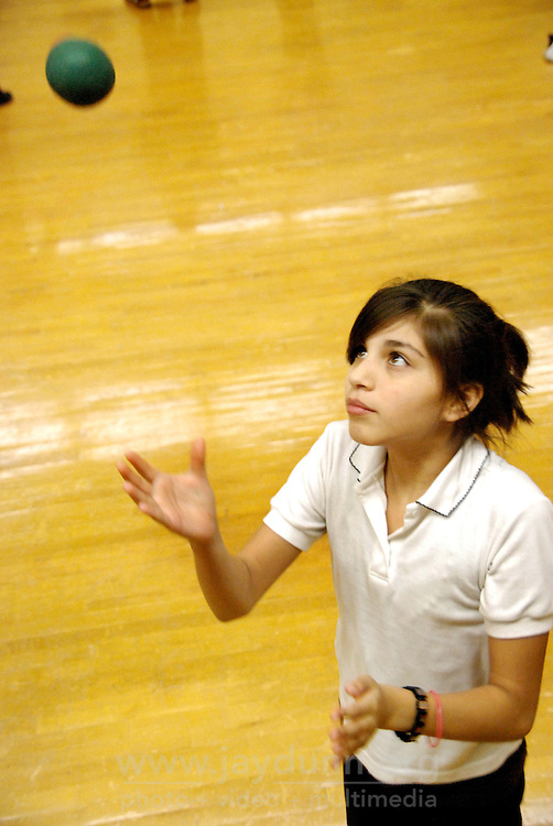 "USA, Chicago, IL, December 12, 2009. Karina Cordero demonstrates fine focus on her juggling. Students in the ""At-Risk After School Program"" at Maria Saucedo Scholastic Academy receive training in basic physics principles through an innovative new program called ""Circus Galactica"" put on by Pros Arts, a non-profit organization founded in 1978 by professional artists dedicated to the Pilsen/Little Village communities. In a residency that directly integrates science and art, veteran circus performers Douglas Grew and Paul Lopez bring the importance of ""balance, focus and presentation"" into hands-on lessons about gravity, inertia, and the dynamics of objects in motion. Photo for Hoy by Jay Dunn."