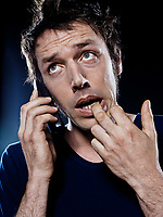 studio portrait on black background of a funny expressive caucasian man phoning anxious