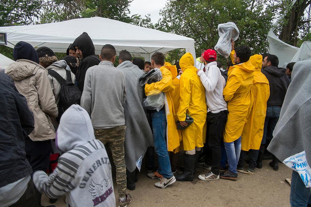 SERBIEN, Grenzstadt Berkasovo, Stadtgebiet von Šid. 08.10.2015 / Fluechtlinge an der serbisch-kroatischen Grenze: Eine Gruppe Fluchtlinge ist gerade aus dem Bus gestiegen, und versucht, bei eisigem Wind, noch Regenjacken oder eine Decke am Stand einer Hilfsorganisation zu ergattern. Die kroatische Grenze, und damit die EU-Aussengrenze, ist nur noch 100 Meter entfernt. Der Grenzuebertritt erfolgt zu Fuss und in Gruppen zu etwa 50 Personen.