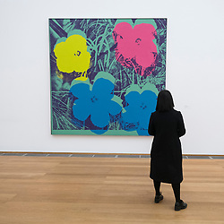 Woman looking at painting Ten-Foot Flowers by Andy Warhol at Hamburger Bahnhof modern art museum in Berlin, Germany