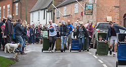 © Licensed to London News Pictures. 26/12/2015. London, United Kingdom. <br /> <br /> Competitors take part in the Boxing Day wheelie bin race through the high street of Bruntingthorpe in Leicestershire.<br /> <br /> Photo credit : Chris Winter/LNP