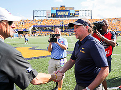 Oct 6, 2018; Morgantown, WV, USA; West Virginia Mountaineers head coach Dana Holgorsen talks with Kansas Jayhawks head coach David Beaty after the game at Mountaineer Field at Milan Puskar Stadium. Mandatory Credit: Ben Queen-USA TODAY Sports
