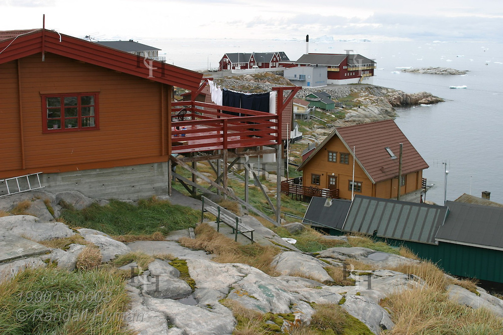 Colorfully painted homes perch along rocky shore overlooking Disko Bay iceberg chunks at Ilulissat, third largest town in Greenland.