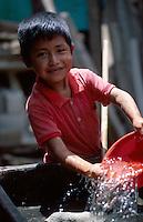 Schoolboy doing chores at his school, Santa Clara, Guatemala