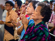 18 SEPTEMBER 2016 - BANGKOK, THAILAND:   Women pray during the 100th anniversary mass for the sanctuary of Santa Cruz Church. Santa Cruz Church was establised in 1769 to serve Portuguese soldiers in the employ of King Taksin, who reestablished the Siamese (Thai) empire after the Burmese sacked the ancient Siamese capital of Ayutthaya. The church was one of the first Catholic churches in Bangkok and is one of the most historic Catholic churches in Thailand. The first sanctuary was a simple wood and thatch structure and burned down in the 1800s. The church is in its third sanctuary and was designed in a Renaissance / Neo-Classical style. It was consecrated in September, 1916. The church, located on the Chao Phraya River, serves as a landmark for central Bangkok.      PHOTO BY JACK KURTZ