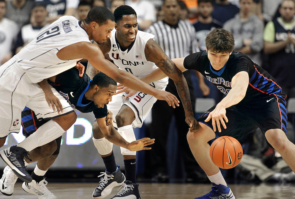 Connecticut's Omar Calhoun, left, and Phillip Nolan, center scramble for control of the ball against DePaul's Durrell McDonald, second from right, and Peter Ryckbosch, right, during the first half of an NCAA college basketball game in Storrs, Conn., Tuesday, Jan. 8, 2013. (AP Photo/Jessica Hill)