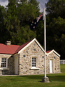 The historic Skipper's Point School and blowing NZ flag, near Queenstown, Otago, New Zealand.