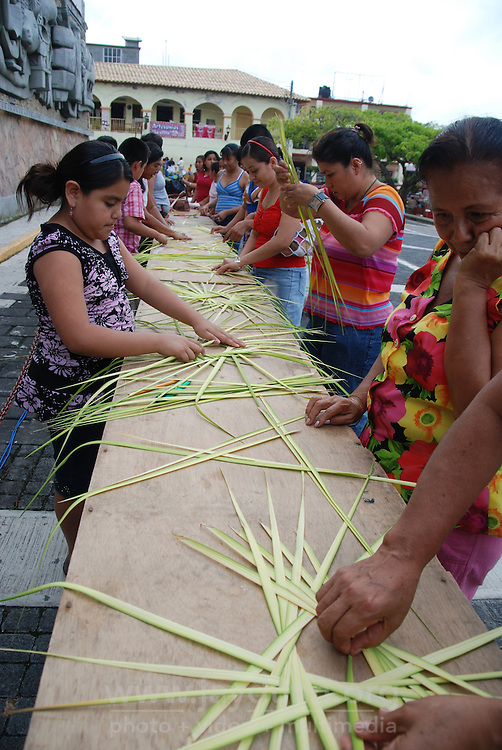 "MEXICO, Veracruz, Tantoyuca, Oct 27- Nov 4, 2009. Citizens learn how to make palm-frond traditional altar decorations in Papantla's ""zocalo."" ""Xantolo,"" the Nahuatl word for ""Santos,"" or holy, marks a week-long period during which the whole Huasteca region of northern Veracruz state prepares for ""Dia de los Muertos,"" the Day of the Dead. For children on the nights of October 31st and adults on November 1st, there is costumed dancing in the streets, and a carnival atmosphere, while Mexican families also honor the yearly return of the souls of their relatives at home and in the graveyards, with flower-bedecked altars and the foods their loved ones preferred in life. Photographs for HOY by Jay Dunn."