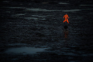 A scarecrow floats on a tailings ponds to prevent any birds landing in it like flocks of ducks fatally did.<br /> During the process of separating bitumen from the tar sands, large amounts of water are mixed in with the sand, and once the oil has been removed, the leftover mixture of water, sand, clay and residual bitumen - known as tailings - has to be stored in a stable location so that the solution can settle and separate.  The storage facilities are known as tailings ponds. July 2008. &copy; Etienne de Malglaive.