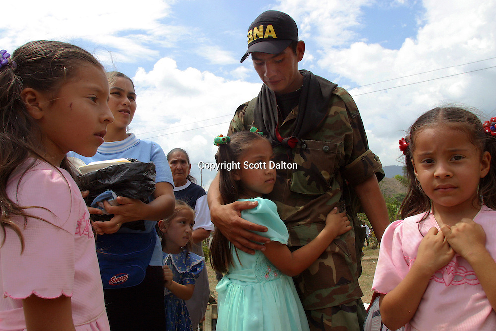 A former member of the paramilitary group Bloque Norte, or Northern Block, is greeted by his family after participating in a disarmament ceremony in Chimila, in northern Colombia, on March 8, 2006. An estimated 24,000 paramilitary members have turned in their weapons as part of a government negotiated peace deal. But some are skeptical if the government plan will really work and if the paramilitary members will be successful in their transformation to civilian life. (Photo/Scott Dalton)