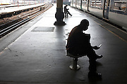 Silhouetted commuters wait on benches for arriving train on covered platform at London Bridge mainline station.