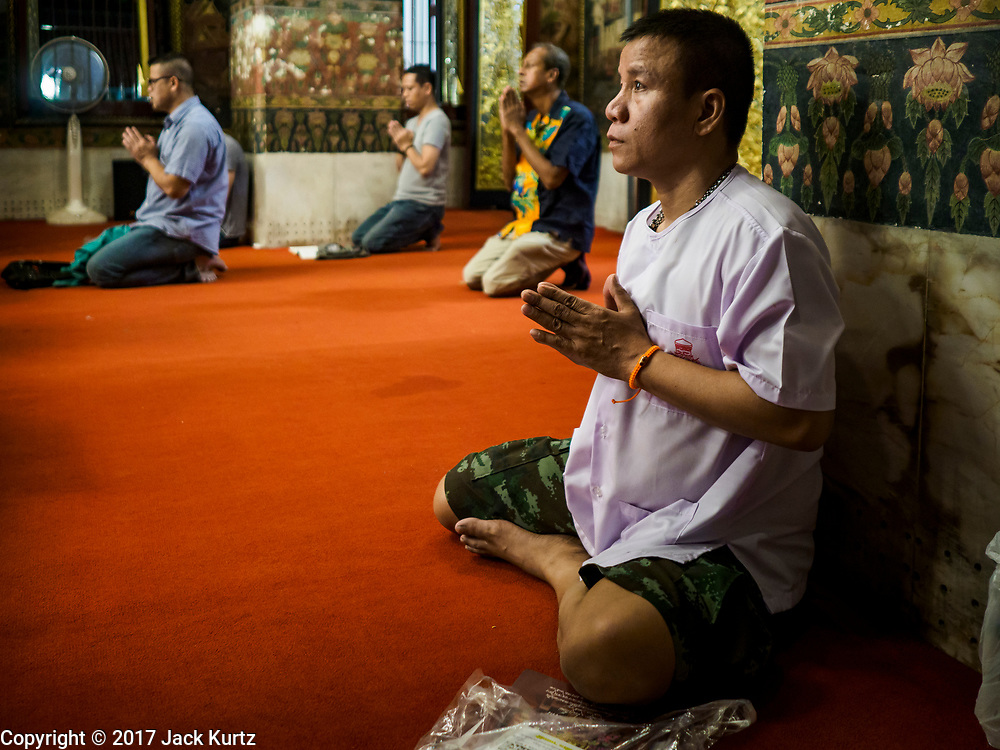 31 DECEMBER 2017 - BANGKOK, THAILAND:  People pray on New Year's Eve in the prayer hall at Wat Pathum Wanaram in central Bangkok. Many Thais go to temples and shrines to pray and meditate during New Year's Eve and New Year's Day.   PHOTO BY JACK KURTZ
