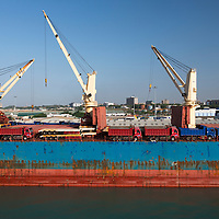 A container ship loaded with trucks docked next to cranes at sunrise in the industrial port of Tema, Ghana.