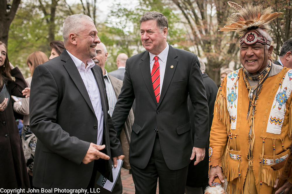 Monacan Chief, Dean Branham, left, greets former Virginia Governor, George Allen, center with Ben Adams, of the Upper Mattaponi Tribe, prior to the dedication ceremony for Mantle: Virginia Indian Tribute, a monument designed on Virginia State Capitol Square, in Richmond, Virginia, on Tuesday, April 17, 2018. As a U.S. Senator, George Allen first introduced the Thomasina E. Jordan bill along with Sen. John Warner, federally recognizing Monacan Indian Nation along with 5 other Virginia Tribes. This past January, the bill was signed into law. John Boal Photography