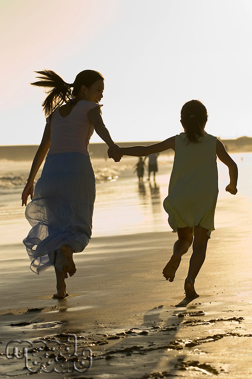 Woman Running on Beach With Daughter