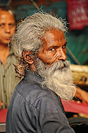 Man with long beard in small print shop in the gullies of Delhi, India
