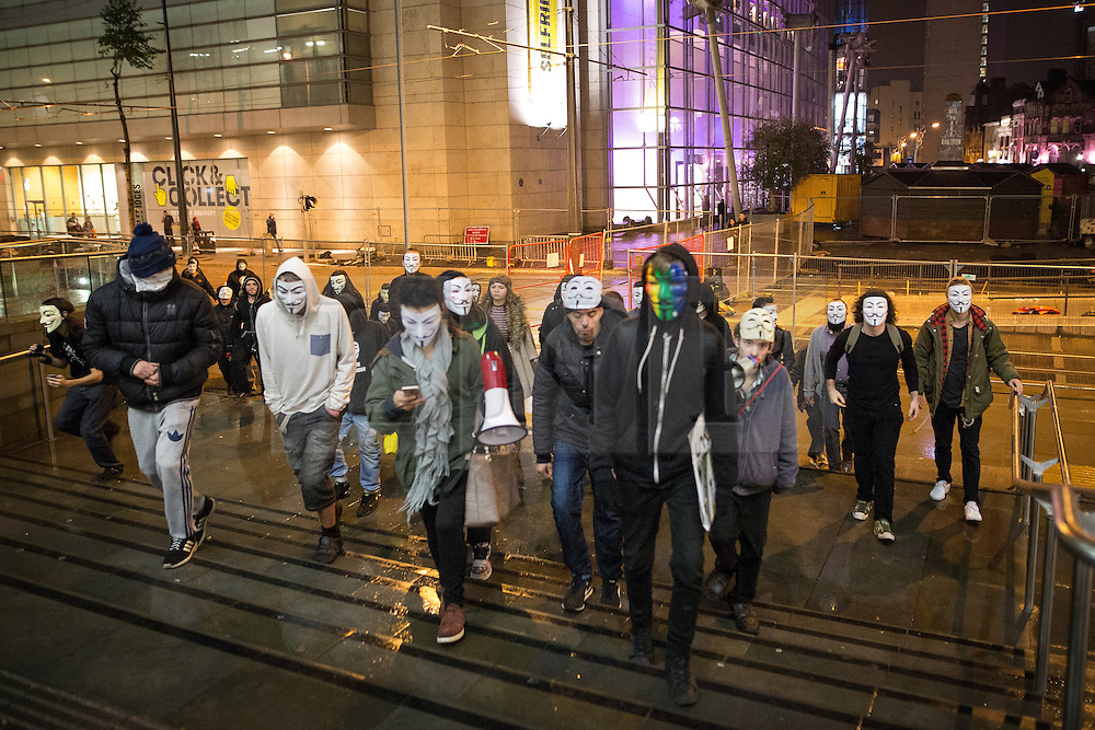 © Licensed to London News Pictures . 05/11/2015 . Manchester , UK . Protesters wearing Guy Fawkes masks at an Anonymous demonstration in to the Arndale Centre in Manchester , UK , this evening (5th November 2015) . Photo credit : Joel Goodman/LNP