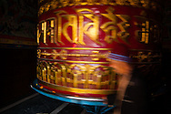 A massive prayer wheel is spun by devotees in the Boudhanath Stupa, thus asking for health, good luck and blessings, in Kathmandu, Nepal.