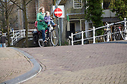 Woman cycling with children on bike, Delft, Netherlands