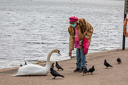 © Licensed to London News Pictures. 13/05/2020. London, UK. A women feeds the birds in Hyde Park. Members of the Public go out in Hyde Park as the Government relaxes the law on lockdown today to let people spend more time outside to enjoy the fresh air, picnics, sunbathing and meet other people while following social distancing guidelines. Photo credit: Alex Lentati/LNP