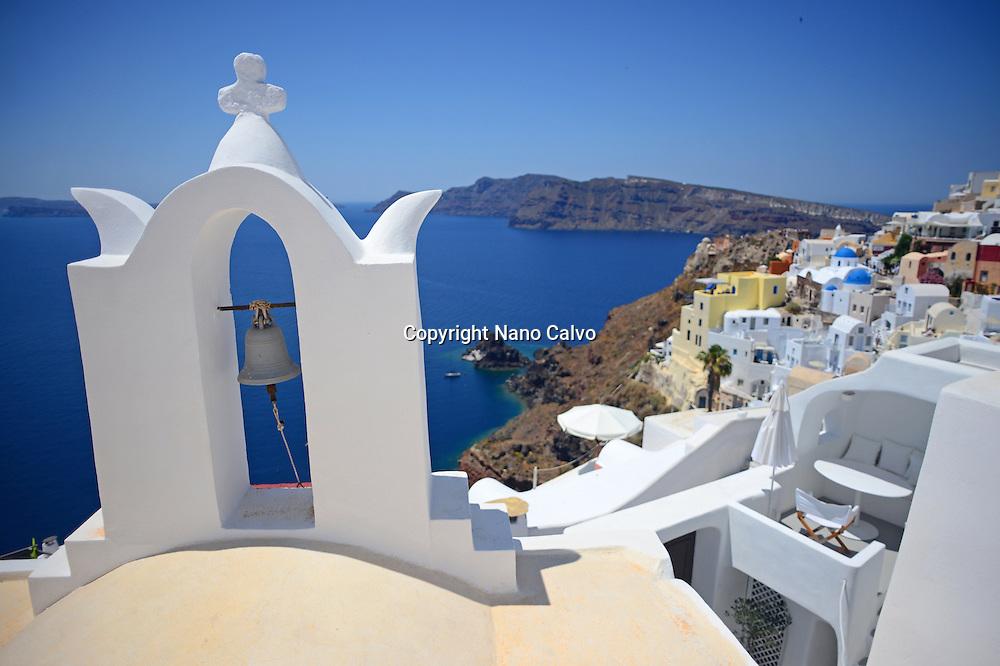 Church bell and hillside buildings in Oia, Santorini, Greek Islands, Greece