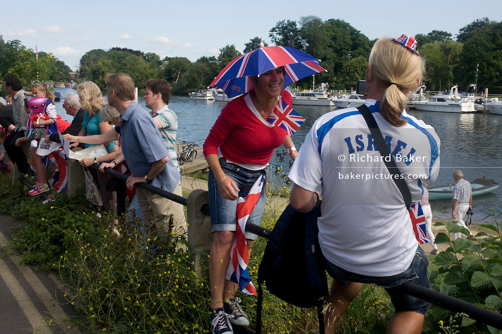 Spectators spend their time next to the river Thames on the first day of competition of the London 2012 Olympic 250km mens' road race. Starting from central London and passing the capital's famous landmarks before heading out into rural England to the gruelling Box Hill in the county of Surrey. Local southwest Londoners lined the route hoping for British favourite Mark Cavendish to win Team GB first medal but were eventually disappointed when Kazakhstan's Alexandre Vinokourov eventually won gold.
