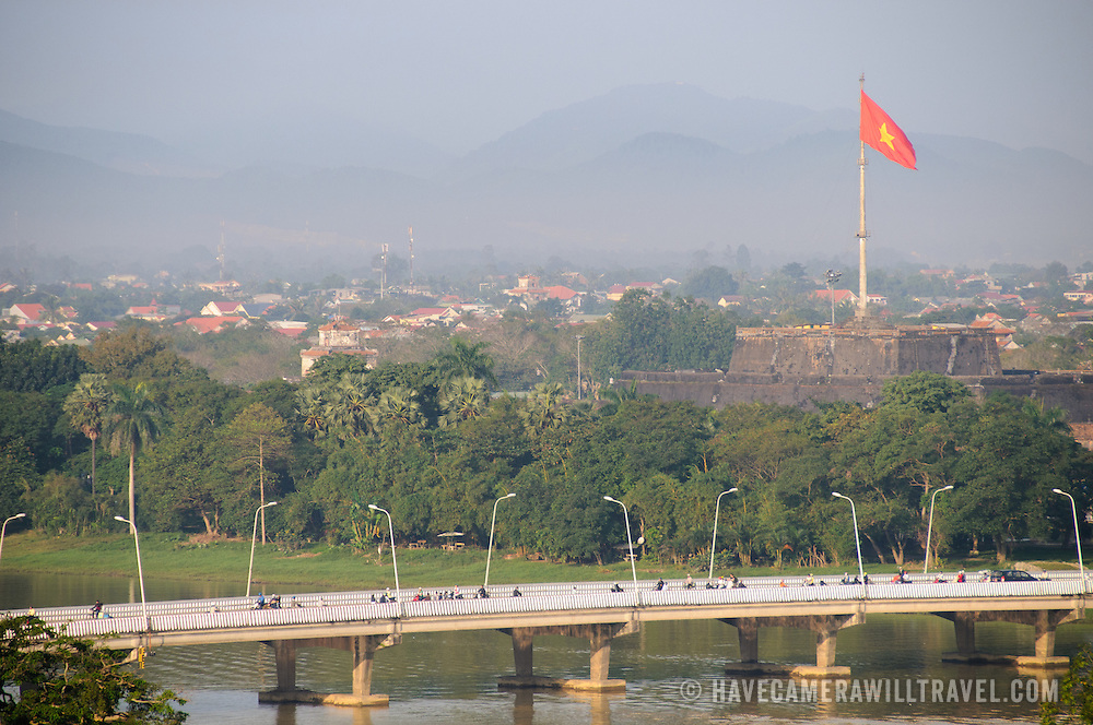 The Vietnamese flag on the Imperial City's citadel towers above the city of Hue, with a bridge over the Perfume River in the foreground.
