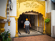 "08 FEBRUARY 2015  BANGKOK, THAILAND: A man walks in the Sikh temple in Bangkok. Thailand has a small but influential Sikh community. Sikhs started coming to Thailand, then Siam, in the 1890s. There are now several thousand Thai-Indian Sikh families. The Sikh temple in Bangkok, Gurdwara Siri Guru Singh Sabha, was established in 1913. The current building, adjacent to the original Gurdwara (""Gateway to the Guru""), was built in 1979. The Sikh community serves a daily free vegetarian meal at the Gurdwara that is available to people of any faith and background.     PHOTO BY JACK KURTZ"