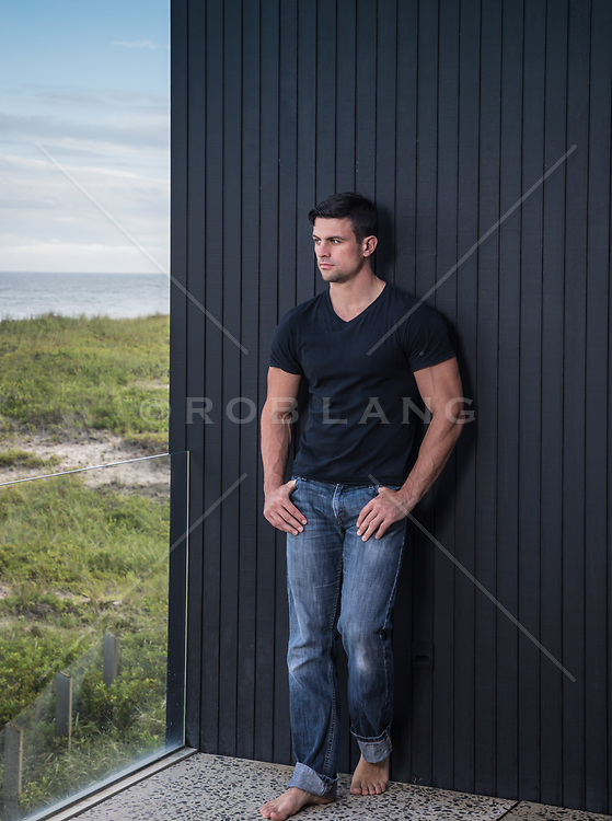 hot man relaxing on a balcony over looking the ocean
