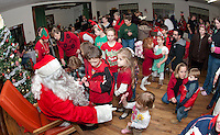 Santa Claus is surrounded by children as he passes out candy canes during the Wicwas Grange Christmas gathering of family and friends Saturday evening.   (Karen Bobotas/for the Laconia Daily Sun)