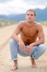 shirtless and shoeless man in jeans on a dirt road in New Mexico
