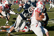 Cortland running back #23 is running the ball for the offense as #94 on Ithaca's defense closes in to make a tackle.