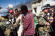 12 FEBRUARY 1996, PORT AU PRINCE, HAITI: US peacekeeping soldiers assigned to the UN mission in Haiti help a Haitian man injured in a melee on the street in the port area of Port au Prince, Haiti, February, 1996.  PHOTO BY JACK KURTZ