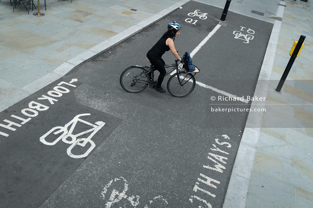 A lady cyclist  rosses a cycle lane whose stencil markings are now fading from much use at this busy traffic and bike junction at Aldwych in central London, on 6th August 2020, in London, England.