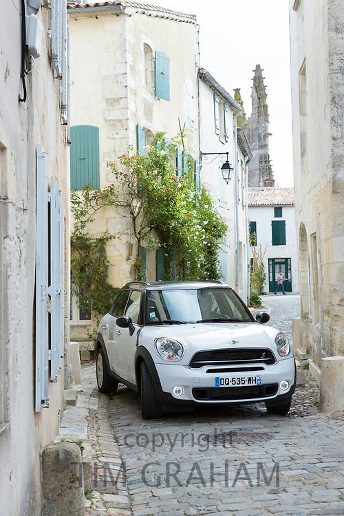 Squeezing through - Mini car driving in narrow streets of St Martin de Re, Ile de Re, France