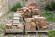 various old and new floor roof tiles and bricks stored together