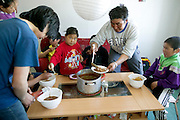 (MODEL RELEASED IMAGE). Lunchtime in the Madsen family household. Emil reaches over the center of the table to serve himself some of the musk ox stew, while a friend who had dropped in for a quick bite doses his meal with ketchup. 6-year-old Belissa takes a spoonful, as Emil's nephew Julian, 10, looks on. (Supporting image from the project Hungry Planet: What the World Eats.)