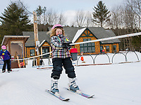 A skier holds on tight as she loads the rope tow at the Abenaki Ski Area in Wolfeboro.  (Karen Bobotas Photographer)