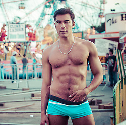 sexy Asian American man in a bathing suit at a carnival in Coney Island, NY
