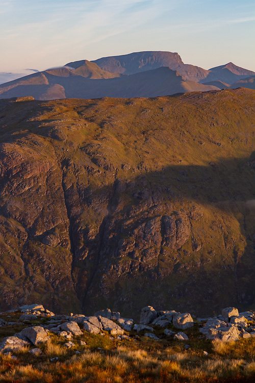 Morning light reaches over over the pass of Glencoe from Stob Coire Raineach as you see Ben Nevis in the far background.