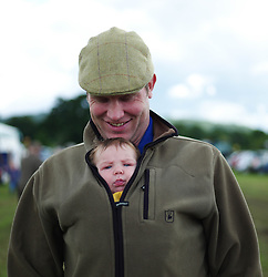 © Licensed to London News Pictures.29/07/15<br /> Borrowby, UK. <br /> <br /> A man carries his baby son as they visit the Borrowby Country Show and Gymkhana in North Yorkshire.<br /> <br /> Photo credit : Ian Forsyth/LNP