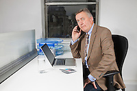 Middle-aged businessman using cell phone in front of laptop at desk in office