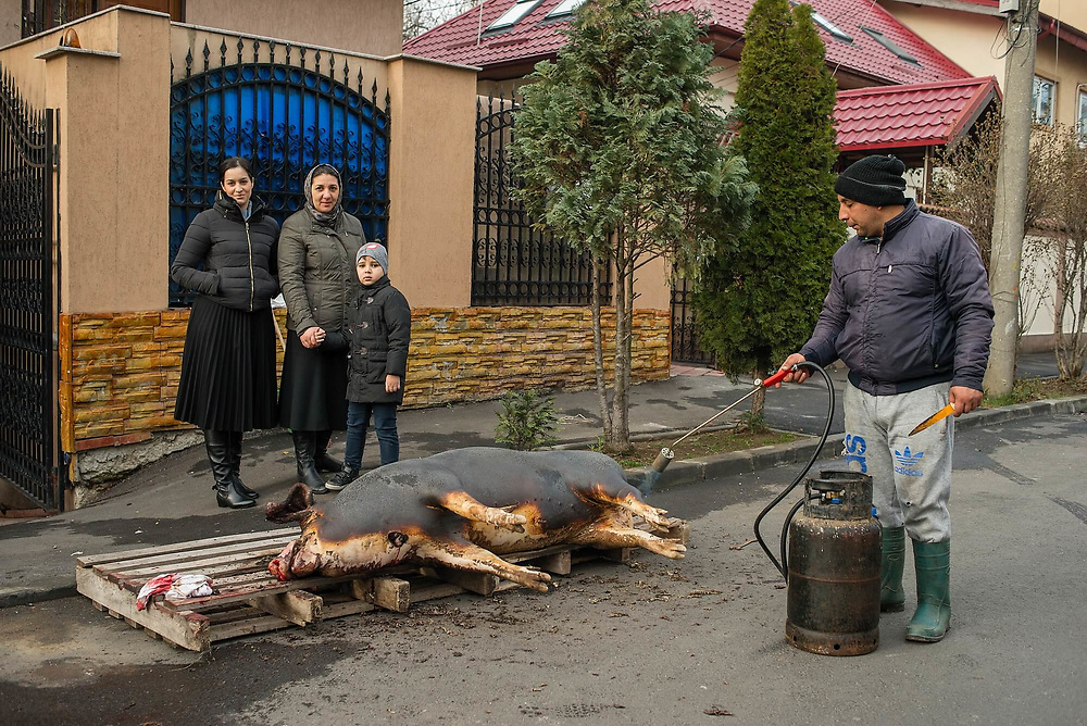 A family in front of their house next to a slaughtered pig, an ancient ritual, linked with Christmas Eve which is often seen in the Romanian countryside and sometimes on the capital's periphery, which still has very tight ties with rural society.