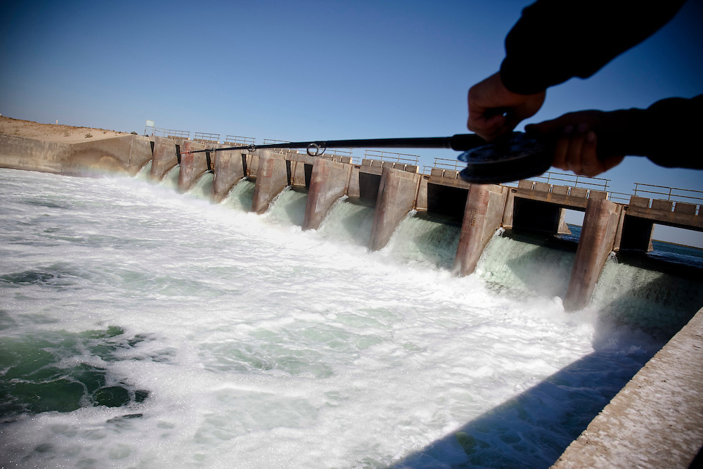 A man fishes by a dam near Aralsk. The decline of the North Aral has now been partially reversed following construction of the dam but the South Aral continue to disappear.