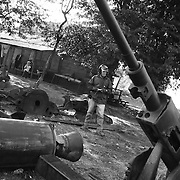 Nol inspects Vietnam War-era artillery sits rusting on the side of Highway9, Ban Dong, Laos, due west of Khe Sanh. ....